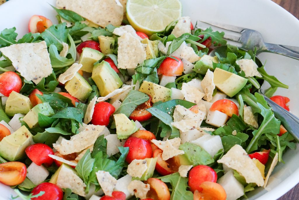 Arugula, Cherry & Jicama Salad in serving bowl with tongs