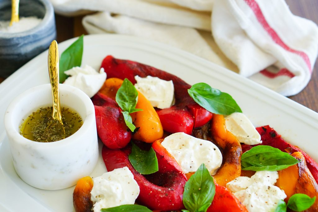 Roasted bell peppers plated with mozzarella cheese and basil