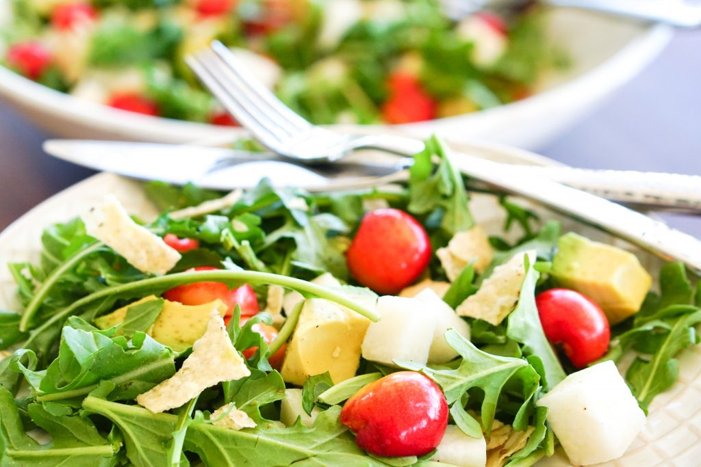 Arugula, Cherry & Jicama Salad on side plate with serving bowl in background