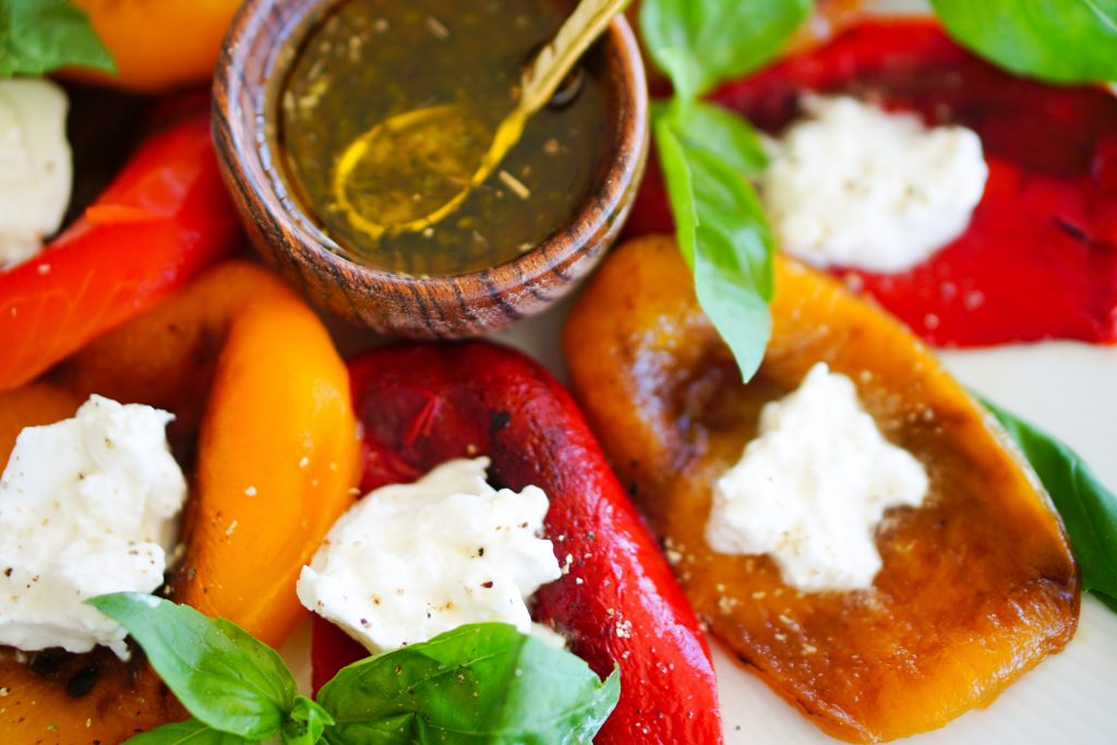 olive oil in a small wooden bowl surrounded by roasted bell peppers mozzarella and basil