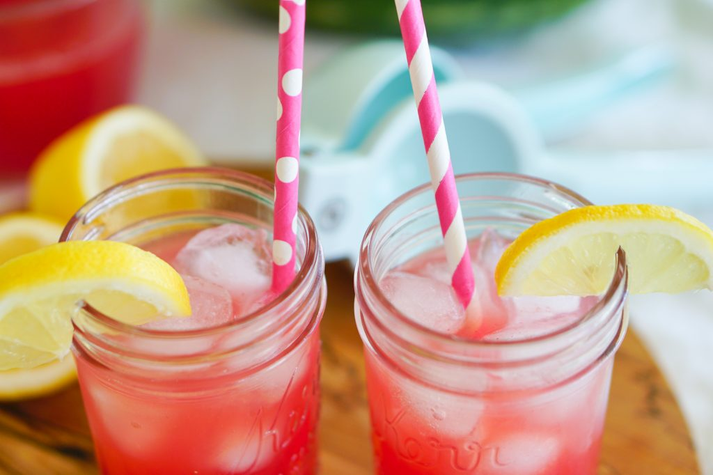 Close up of watermelon lemonade in mason jars with paper straws and citrus squeezer