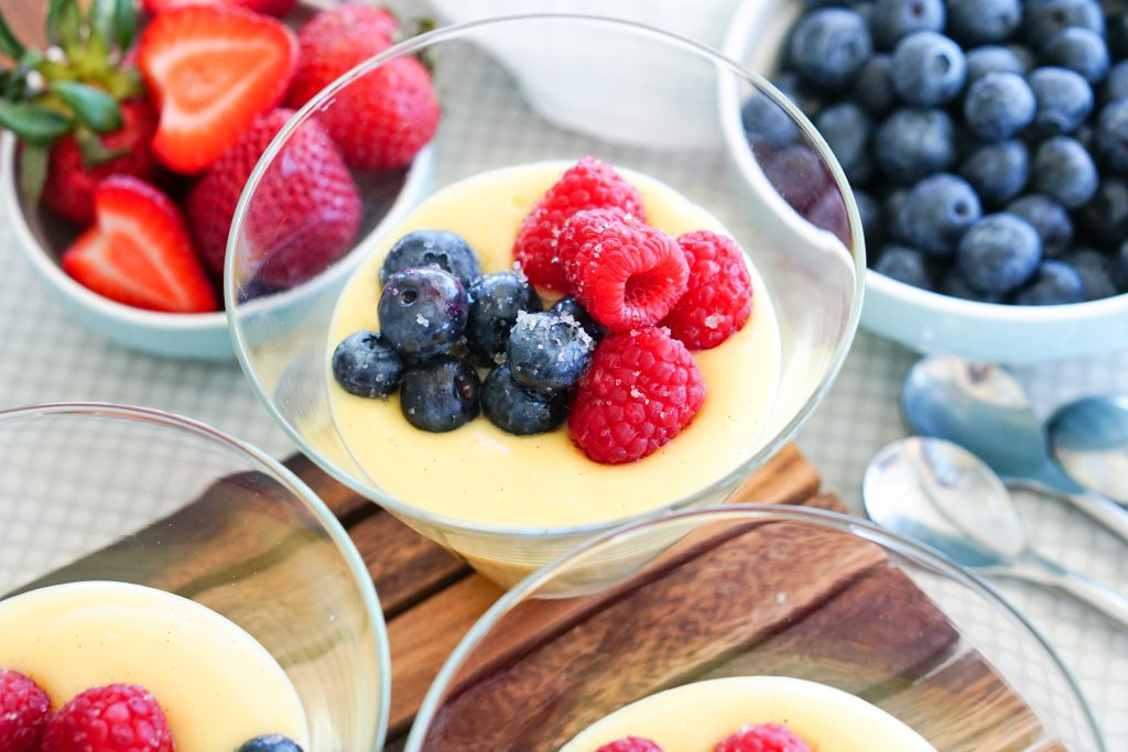 close up of three vanilla puddings topped with blueberries and raspberries on wooden background