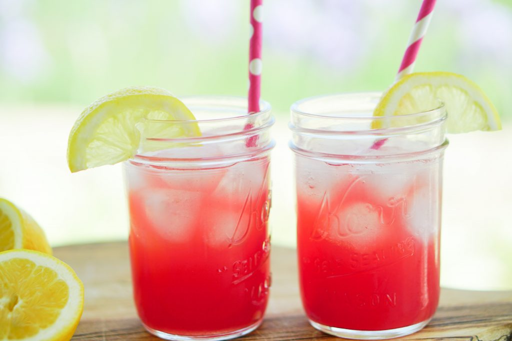 Side view of watermelon lemonade in mason jars with paper straws and lemon wedges