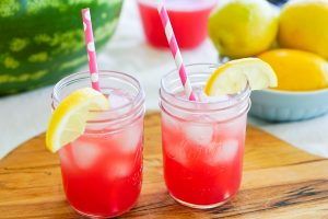 Scene on cutting board with watermelon lemonade in mason jars with paper straws and fruit in background