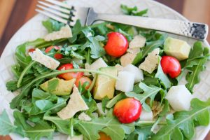 Arugula, Cherry & Jicama Salad on table