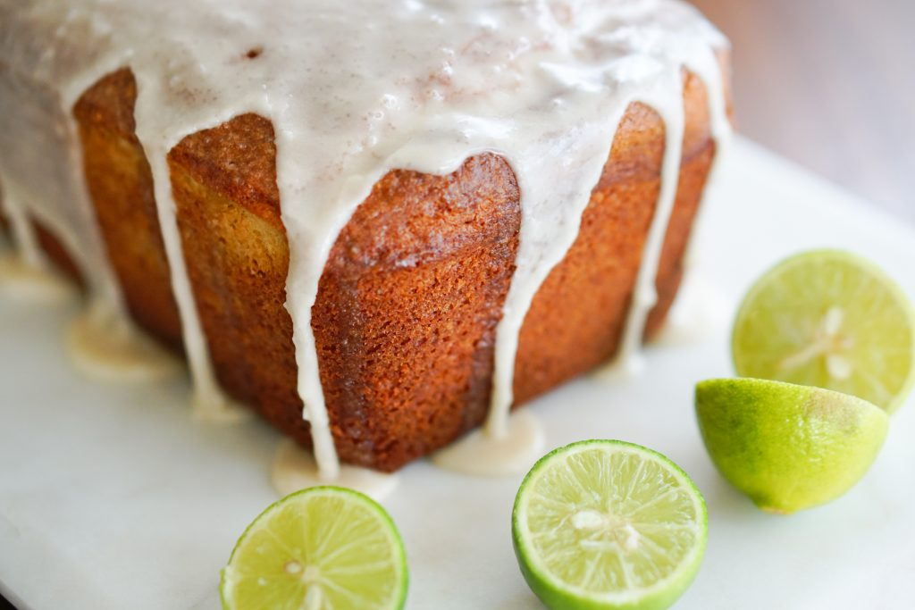 The whole unsliced Key Lime Glazed Buttermilk Pound Cake on a white serving platter with cut limes