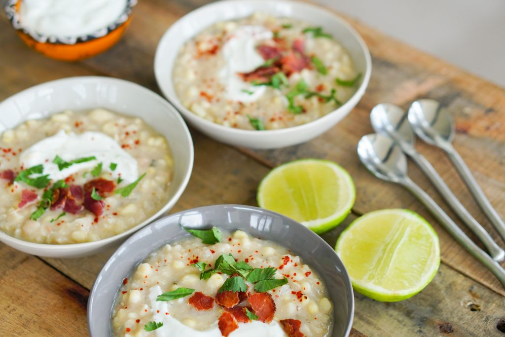 Angled view with chowder in bowls and lime halves and spoons