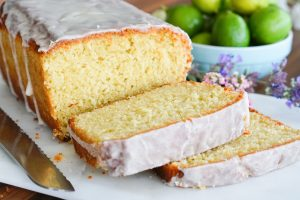 Key Lime Glazed Buttermilk Pound Cake with two slices ready to be eaten resting on a white serving platter