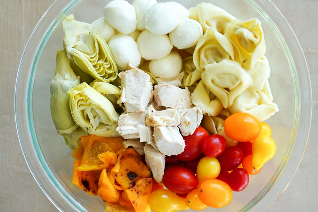 Close up of ingredients for tortellini salad in bowl including pasta chicken artichoke tomatoes roasted peppers and mozzarella
