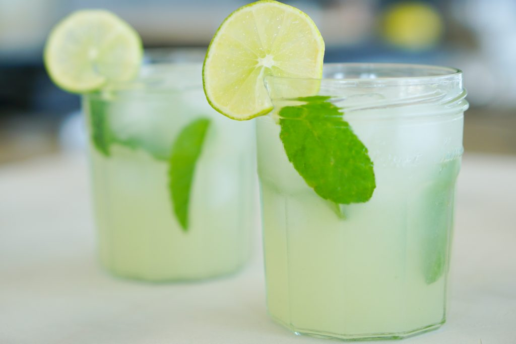 Key Lime Mojitos in glasses with mint leaves ice cubes and lime slice