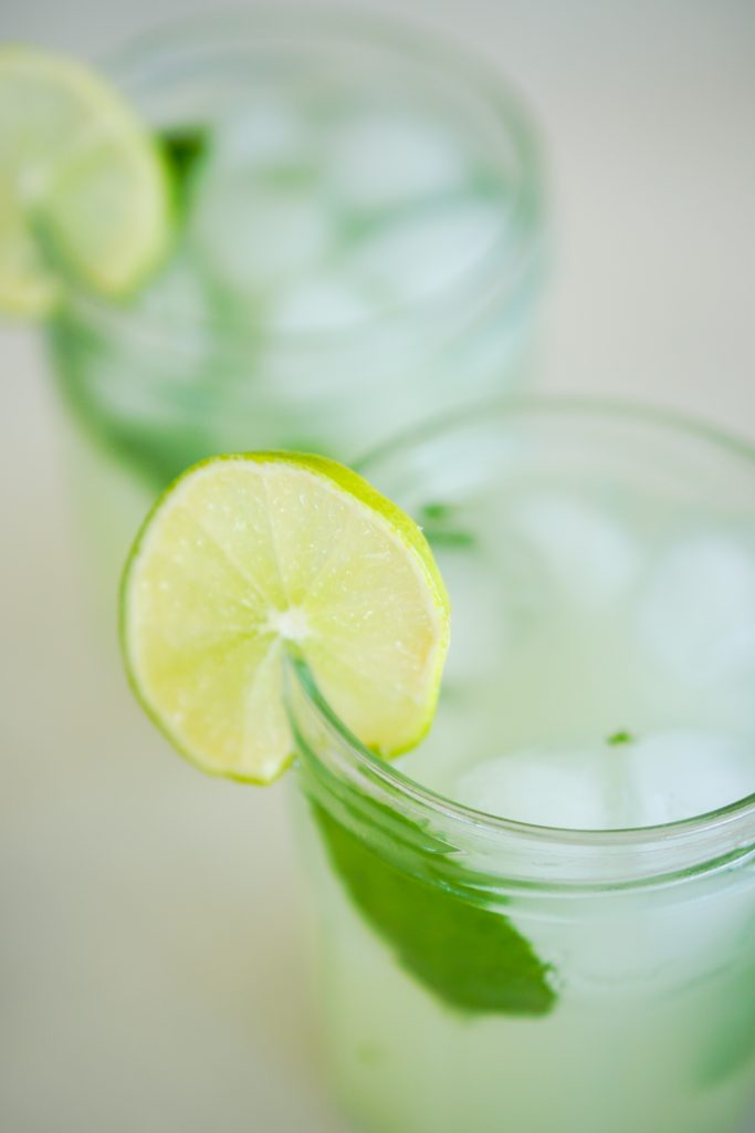 Angle view of Key Lime Mojitos in glasses with mint leaves ice cubes and lime slice