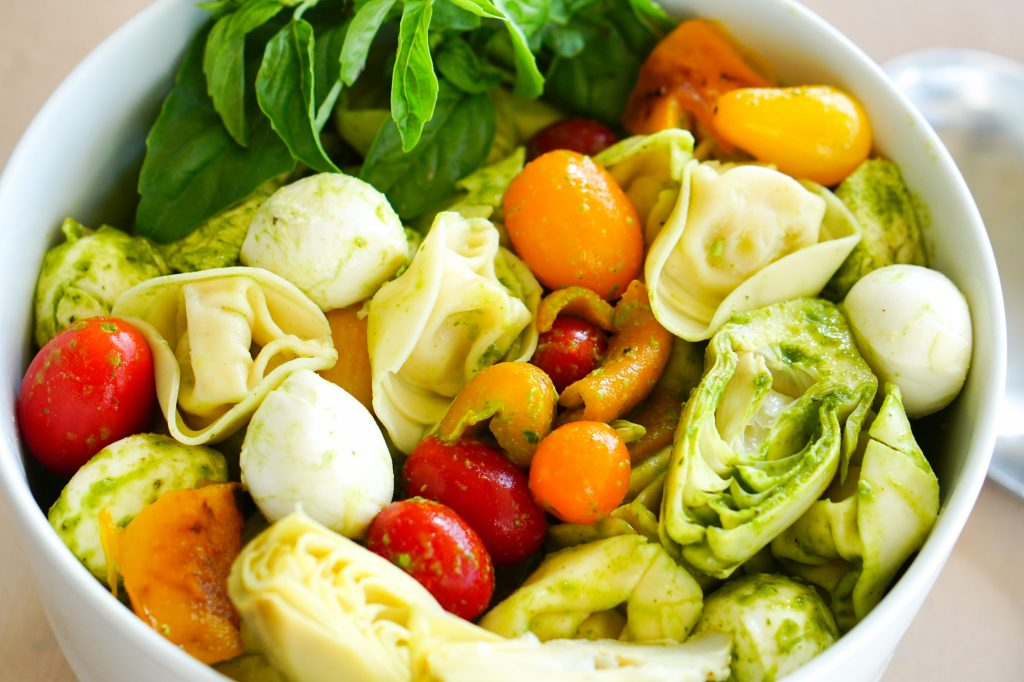 Close up of tortellini salad with chicken artichoke tomatoes roasted peppers and mozzarella