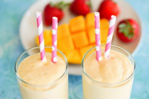 Coconut Yogurt Mango Smoothies in cups with pink and white paper straws