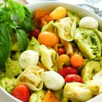 Tortellini salad in serving bowl with Key Lime Lexi Good Food Good Mood tea towel on side