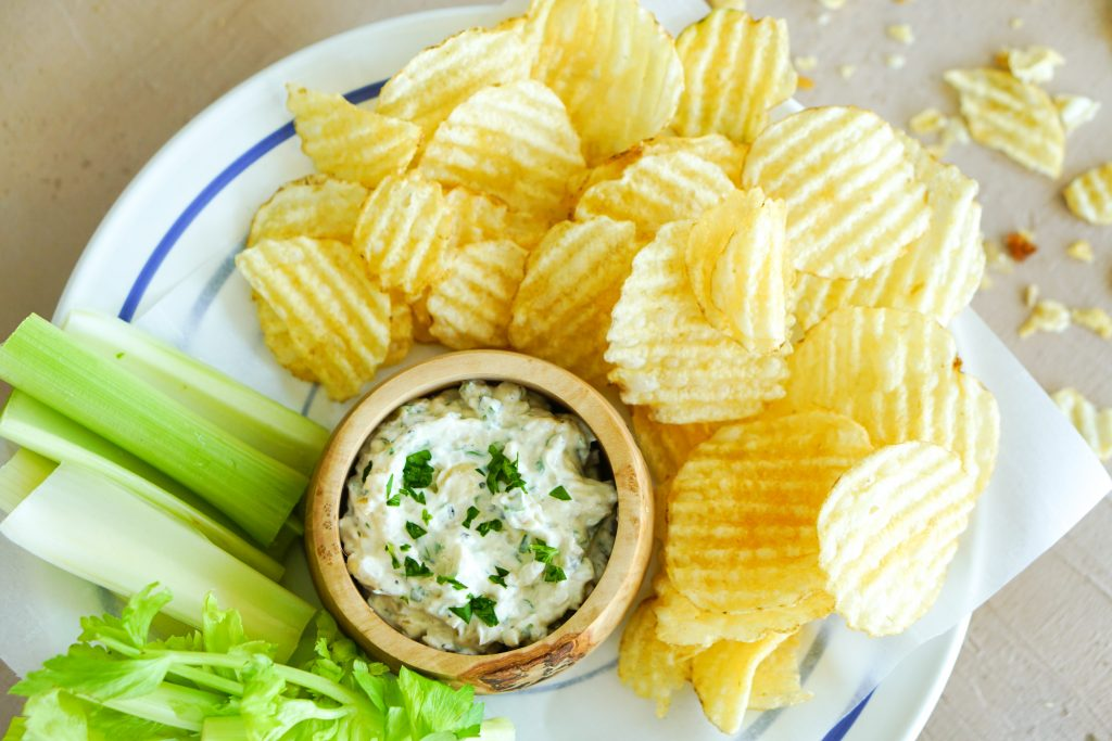 Top down of Sour cream & onion dip in a bowl with potato chips