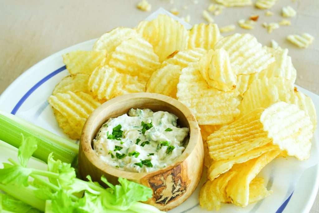Sour cream & onion dip in a bowl with potato chips