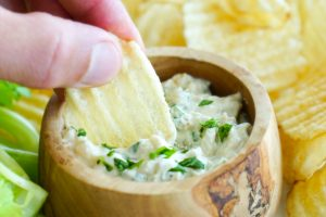 Dipping a potato chip in a bowl of sour cream & onion dip