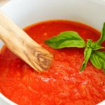 Best Big Batch From Scratch Tomato Sauce in a serving bowl garnished with a basil sprig