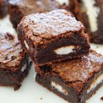 Close up of Peppermint Pattie Rich Chocolate Brownies stacked on a white serving platter
