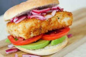 Side angle of Crispy Fish Sandwich with onions tomatoes and avocado on serving board