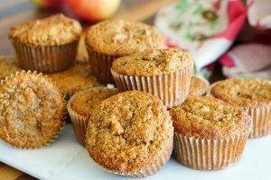 Carrot Apple & Date Morning Muffins stacked on a white serving platter with apples and a tea towel in background