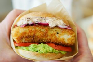Crispy Fish Sandwich wrapped up in parchment and being held ready to eat