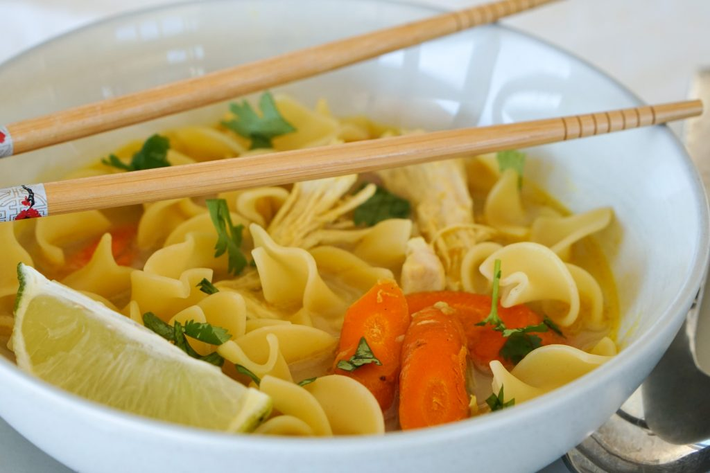 Turkey Noodle Soup with carrots and cilantro in a bowl with chopsticks