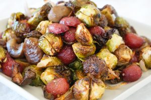 Crispy Brown Butter Brussels Sprouts with Roasted Grapes & Chestnuts on a white serving plate