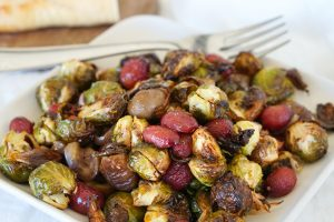 Crispy Brown Butter Brussels Sprouts with Roasted Grapes & Chestnuts on a white serving plate with bread and glasses in background