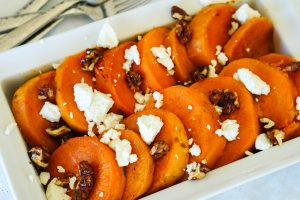 Orange Maple Slow Cooked Spiced Sweet Potatoes in a serving dish topped with candied nuts and fresh goat cheese