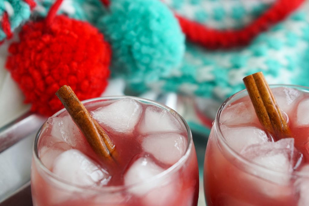 Two glasses of Santa's Little Helper whiskey cocktail over ice with a cinnamon stick garnish and blue and red stockings in the background