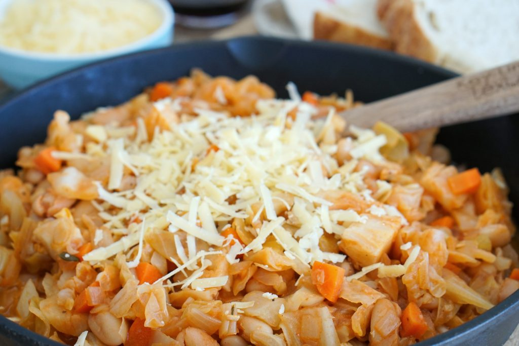 Close up of Vegetarian Cassoulet in pot with wooden serving spoon, shredded cheese and bread in background