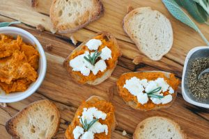 Top down of crostini topped with smoky carrot spread, soft goat cheese and rosemary sprigs on a wooden serving board