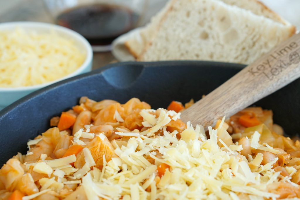 Vegetarian Cassoulet in pot with wooden serving spoon, shredded cheese and bread in background