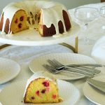 Cranberry Bundt Cake cut with pieces missing on white and gold cake stand and plated cake in foreground