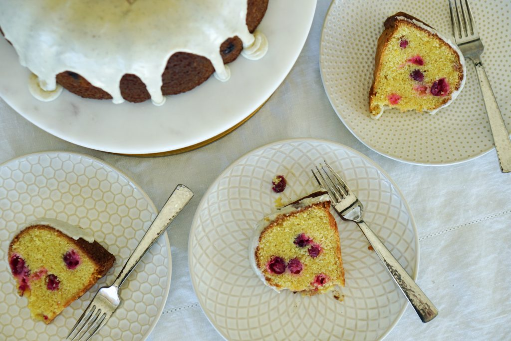 Top down of Cranberry Bundt Cake on cake stand with plated pieces of cake to the side