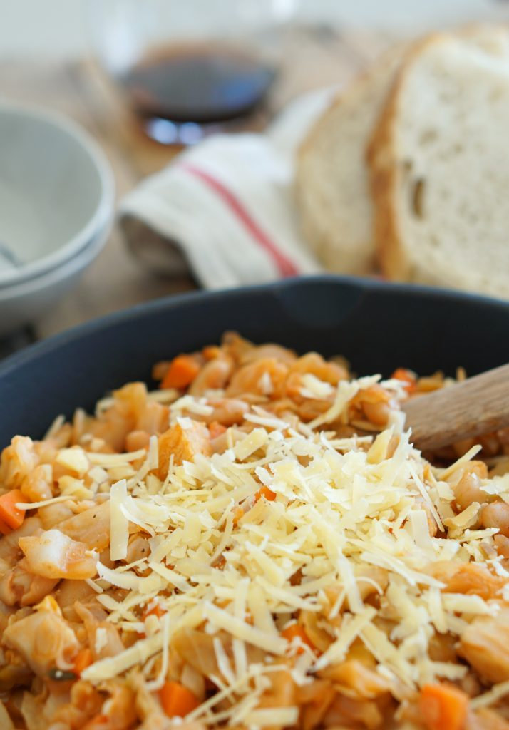 Vegetarian Cassoulet in pot with wooden serving spoon, bowls and bread in background