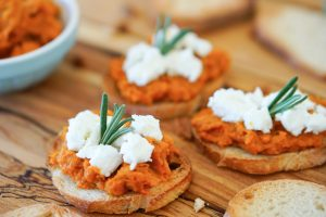 Crostini topped with smoky carrot spread, soft goat cheese and rosemary sprigs on a wooden serving board