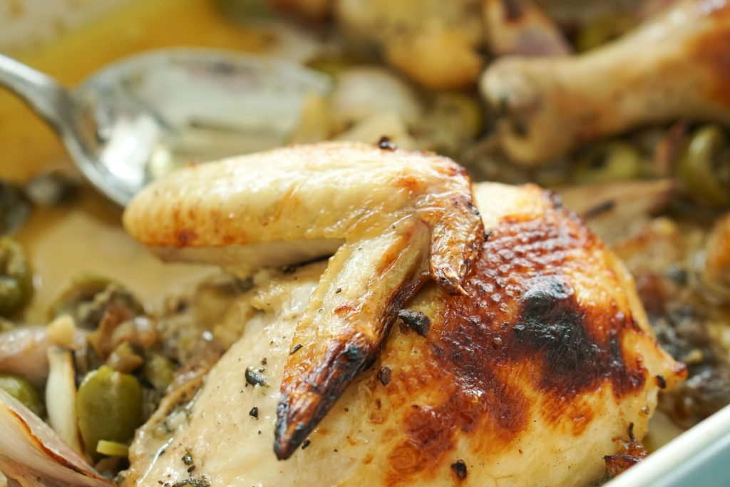 Close up of Chicken Marbella with serving spoon
