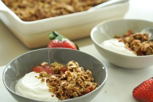Two bowls of Strawberry Crisp with Honey Vanilla Yogurt with Key Lime Lexi ombre baker in background