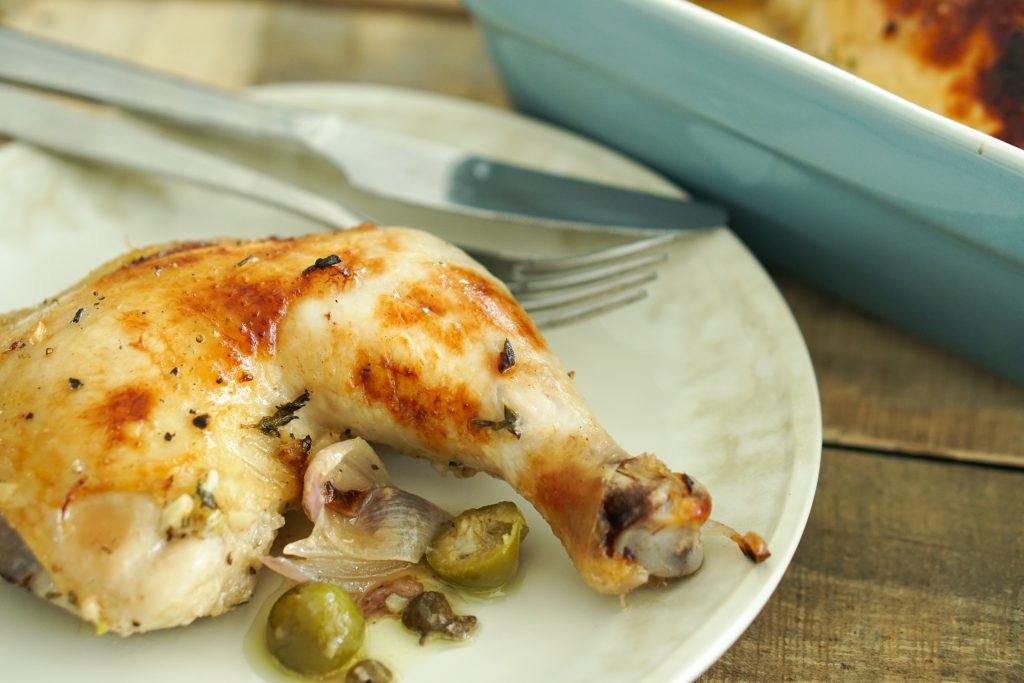 Chicken Marbella plated with fork and knife and baking dish in background
