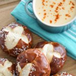 Soft pretzels bites on a cutting board with a small pot of smoked cheddar beer cheese