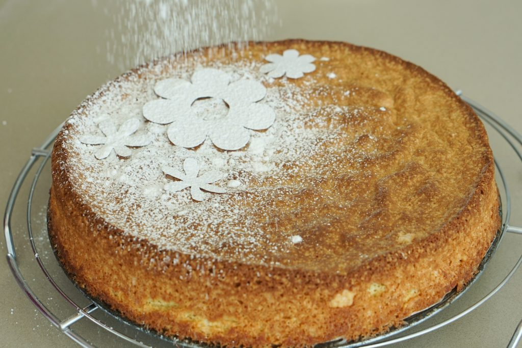 Spanish Almond Cake on cooling rack with with flower stencils and powdered sugar being dusted on top