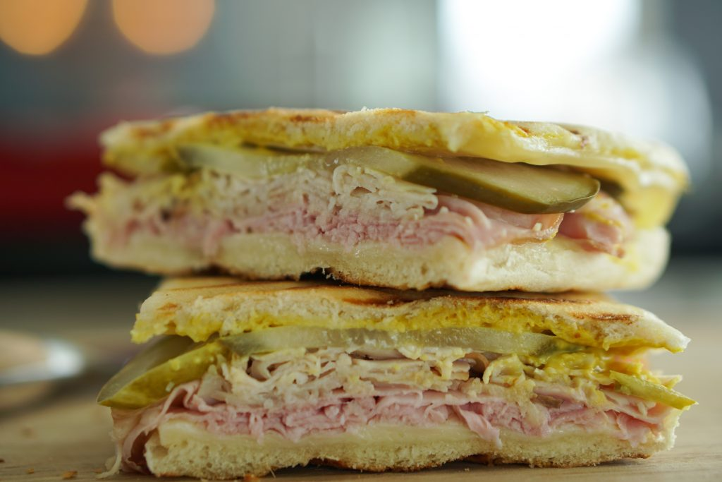 Two halves of a Cuban sandwich stacked on cutting board