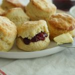 Irish Butter Scones with jam spread on plate with on a knife in foreground