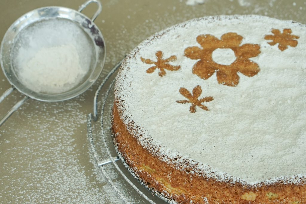 Spanish Almond Cake on cooling rack with powdered sugar and fine mesh strainer for dusting