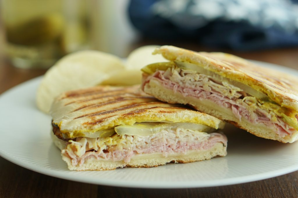 Two halves of a Cuban sandwich stacked on a plate