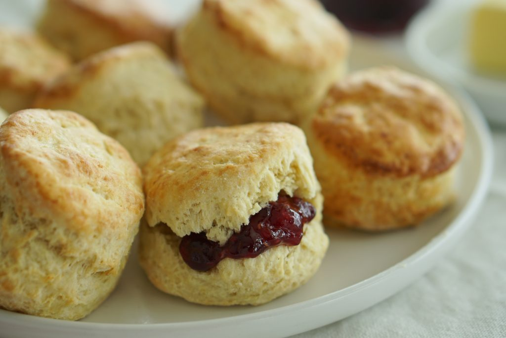 Irish Butter Scones with jam spread on plate with