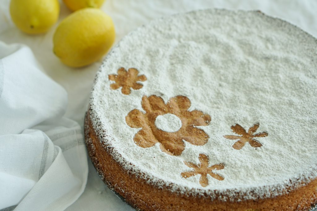 Spanish Almond Cake on white table cloth with napkin and lemons