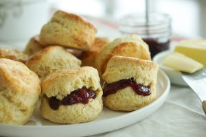 Irish Butter Scones with jam spread on plate with butter in background